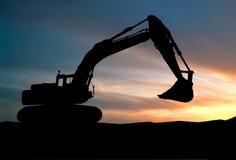 Siluetta del caricatore di escavatore al cantiere con alzato Fotografie Stock