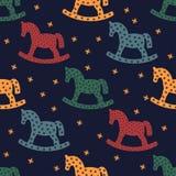 Siluetta del cavallo a dondolo Modello senza cuciture con i cavalli a dondoli su fondo blu scuro royalty illustrazione gratis