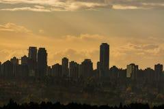 Siluetta del centro nel tramonto sul fondo del cielo nuvoloso fotografie stock
