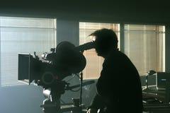 Siluetta del cineoperatore con la macchina fotografica nella nerezza Fotografia Stock