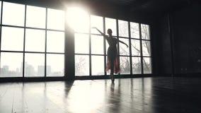 Siluetta del dancing della ballerina sulle punte dei piedi nei pointes contro lo sfondo di grande finestra Giovane ballerina graz stock footage
