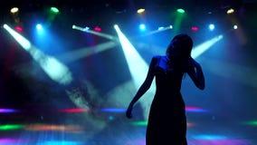 Siluetta del dancing della ragazza ad un partito al night-club video d archivio