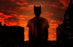 Siluetta del diavolo sui precedenti del cielo sanguinoso rosso fotografia stock libera da diritti