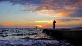 Siluetta del fotografo che prende le immagini durante il pilastro di tramonto video d archivio