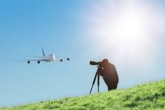 Siluetta del fotografo dello spotter che cattura le foto dell'aereo di linea di atterraggio Fotografie Stock Libere da Diritti