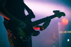 Siluetta del giocatore di basso elettrico in scena Fotografia Stock