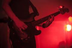Siluetta del giocatore di basso elettrico su rosso Fotografia Stock