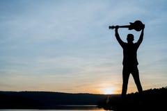 Siluetta del giocatore di chitarra sulla pietra Fotografia Stock Libera da Diritti