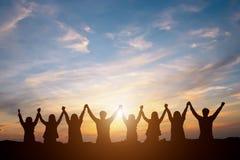 Siluetta del gruppo felice di affari che fa le arroganze nel tramonto SK fotografia stock libera da diritti