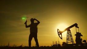 Siluetta del lavoratore felice del giacimento di petrolio alla pompa del petrolio greggio nel giacimento di petrolio al tramonto  stock footage