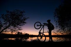 Siluetta del motociclista al tramonto Fotografia Stock