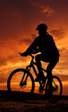 Siluetta del motociclista della montagna nell'alba Fotografia Stock