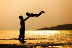 Siluetta del padre asiatico che getta sua figlia su nell'aria immagini stock