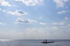 Siluetta del padre e di due pochi figli su una piccola isola nel mare fotografia stock