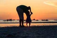 Siluetta del padre e di piccola figlia sul tramonto Immagine Stock