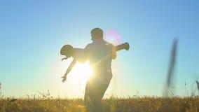 Siluetta del padre e del figlio che giocano, godente del tramonto nel giacimento di grano in natura il giorno di estate Camminare video d archivio