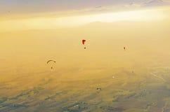 Siluetta del paraglide che sorvola le alte montagne Fotografia Stock