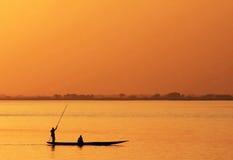 Siluetta del pescatore africano in canoa Fotografia Stock