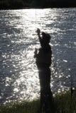 Siluetta del pescatore al crepuscolo che controlla la sua linea fotografia stock libera da diritti