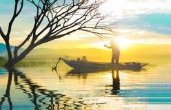 Siluetta del pescatore che utilizza condizione a rete nell'orecchio della piccola barca fotografia stock libera da diritti