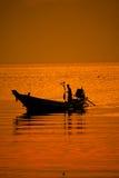 Siluetta del pescatore e della barca a vela fotografia stock libera da diritti