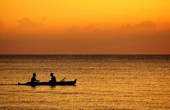 Siluetta del pescatore su una barca Fotografia Stock