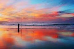 Siluetta del pescatore sulla spiaggia al tramonto Immagine Stock