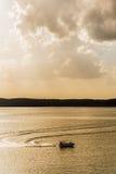 Siluetta del peschereccio sul lago - alba/tramonto dorati fotografia stock