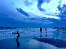 Siluetta del ragazzo che gioca ad una spiaggia fotografia stock libera da diritti