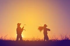 Siluetta del riso e della falce della tenuta dell'agricoltore sul campo Fotografia Stock Libera da Diritti