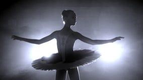 Siluetta del ` s della ballerina che gira intorno la ballerina con capelli in un panino sta ballando su una scena, contro la luce stock footage