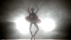 Siluetta del ` s della ballerina che gira intorno la ballerina con capelli in un panino sta ballando su una scena, contro la luce archivi video