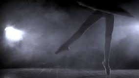 Siluetta del ` s della ballerina che gira intorno la ballerina con capelli in un panino sta ballando su una scena, contro la luce video d archivio