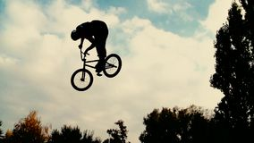 Siluetta del saltatore, eseguente il mountain bike di BMX video d archivio