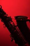 Siluetta del sassofono su colore rosso Immagine Stock