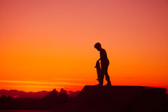 Siluetta del skateboarder al tramonto Fotografie Stock Libere da Diritti