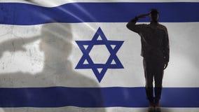 Siluetta del soldato israeliano che saluta contro la bandiera nazionale, prevenzione del terrorismo video d archivio