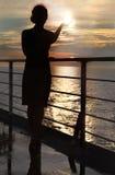 Siluetta del sole della holding della donna, levantesi in piedi sulla piattaforma Fotografia Stock