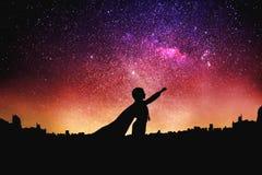 Siluetta del supereroe ai precedenti stellati del cielo di notte Fotografia Stock