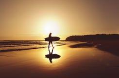 Siluetta del surfista che cammina lungo la spiaggia all'alba Fotografia Stock