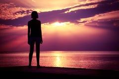 Siluetta del tramonto di sorveglianza del mare della giovane donna immagine stock