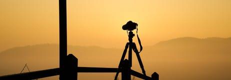 Siluetta del treppiede con la macchina fotografica Immagine Stock
