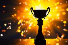 Siluetta del trofeo della tazza contro fondo brillante Fotografia Stock