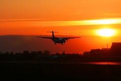 Siluetta dell'aereo di atterraggio su un tramonto. Immagine Stock