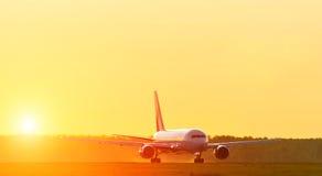 Siluetta dell'aeroplano dell'aeroporto della pista di mattina alla luce del sole di tramonto di alba Fotografia Stock