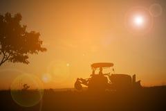 Siluetta dell'agricoltore che guida trattore sul campo Fotografia Stock Libera da Diritti