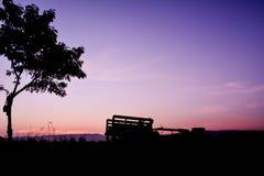 Siluetta dell'agricoltore che guida trattore sul campo Fotografia Stock