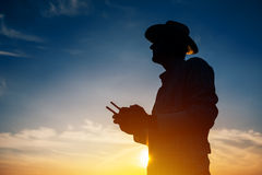 Siluetta dell'agricoltore che per mezzo del telecomando del fuco Immagini Stock Libere da Diritti
