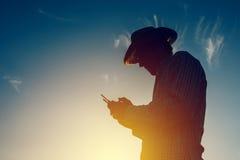 Siluetta dell'agricoltore che per mezzo del telecomando del fuco Fotografia Stock