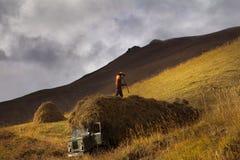 Siluetta dell'agricoltore con una forca che raccoglie fieno Fotografie Stock Libere da Diritti